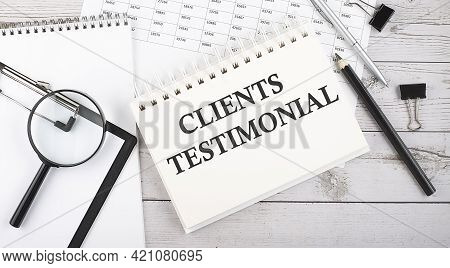 Notepad With Text Clients Testimonial With A Pen,office Tools And Graphs On Desktop.