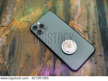 Paris, France - May 2, 2021: Hero Object Of New Airtag Above Avove Iphone 12 Pro Focus On Designed B
