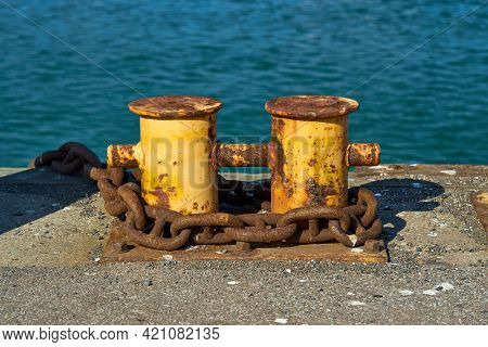 A Double Bitt Mooring Bollard With A Heavy Chain Around It. The Rusty Mooring Bitt Is Used To Anchor