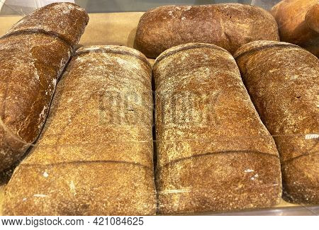 Close Up Of Crusty Loaves Of Bread To Sell On Counter In Bakery Shop