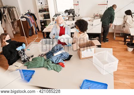 Colleagues Standing Near Recycling Boxes And Sorting Clothes For The Re Sewing