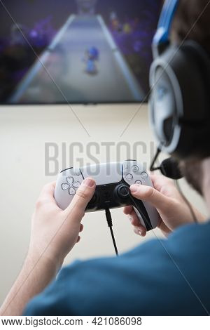 York, Uk - May 9, 2021. Rear View Of Teenage Boy Holding A Playstation 5 Game Controller And Playing