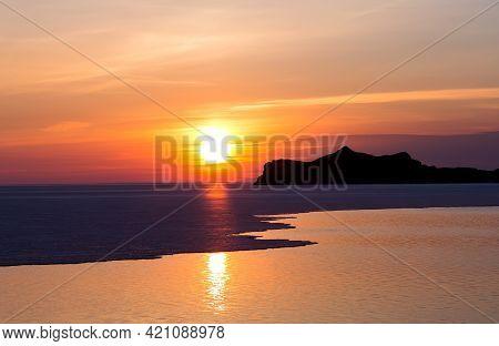 Amazing Golden Sunrise. Early Morning Landscape With Sun, Sky, Lake And Rocks. Sunrise Background.