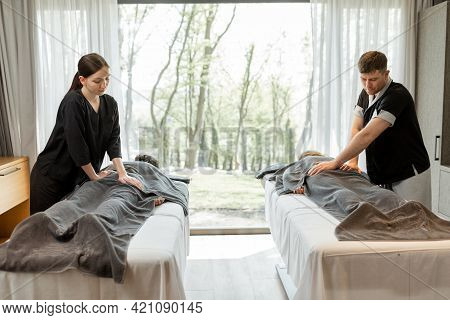 Two Masseurs Doing A Deep Back Massage To Guests With Pampering Technique. Wellness And Leisure Time