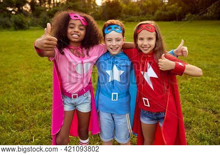 Group Of Multiracial Friendly Kids Wearing Superhero Capes And Masks Hugging Together In Park And Sh