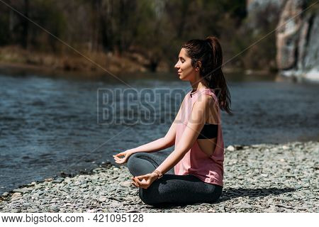 Attractive And Young Woman Doing Yoga By The River At Dawn, Close-up. Yoga In The Fresh Air. Happy W