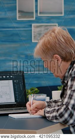 Senior Woman Architect Analysing Digital Prototype With Plans From Laptop Working From Home, Taking