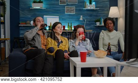 Multiracial Friends Sitting On Couch Watching Fun Movie On Television During Home Party Late At Nigh