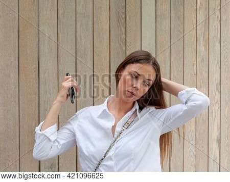 Portrait Of A Woman In A White Blouse. The Brunette Stands In The Park Against A Wooden Plank Wall.
