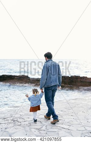 Dad In A Denim Suit Walks By The Hand With A Little Girl In A Dress And A Denim Jacket Along The Pie