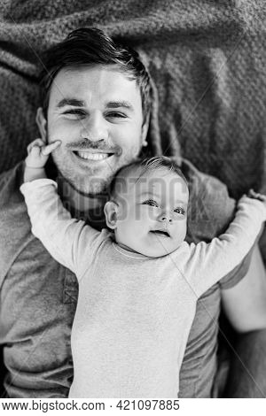 Tiny Baby Lies With His Back On The Chest Of A Smiling Dad, Arms Outstretched. Black And White Photo