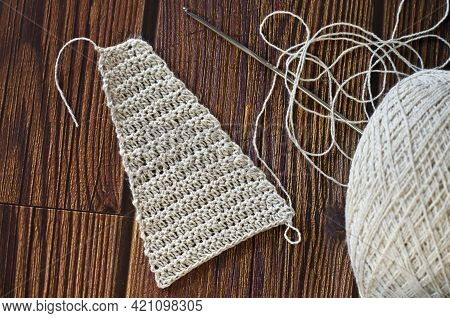 Handmade Crocheted With White Linen Threads On A Wooden Table.