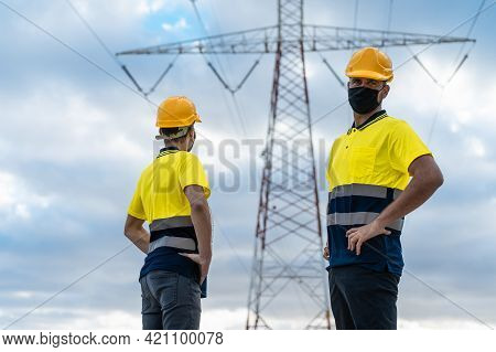 Electrical Engineers Working. Electrician Looking The Camera And Another Skilled Worker Looking High