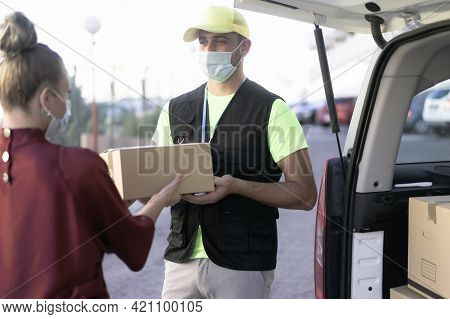 Portrait Of Delivery Man Wearing Face Protective Mask For Coronavirus Spread Prevention. Woman Hand