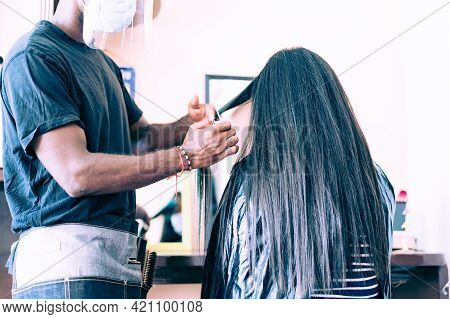 A Hairdresser With Security Measures For Covid-19. Man Cuting The Hair,  With Protective Mask And Ey