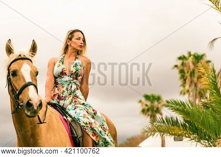 Portrait Of Young Beautiful Brunette Woman Wearing Flowers Dress Riding Brown Horse At Summer Cloudy