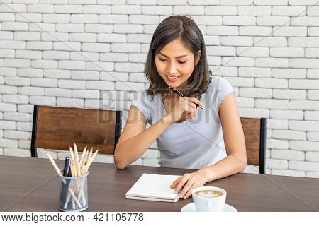 Young Attractive Asian Woman Smiling Thinking Planning Writing Memo In Notebook Working From Home