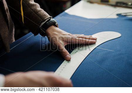 Tailor Cutting Suit Fabric On Sketch Line. Fashion Designer Tailor Or Sewer In Workshop Studio Desig