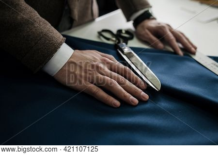 Tailor's Hands On The Fabric. Custom Tailoring Of Products. Tools For Cutting Clothing Material