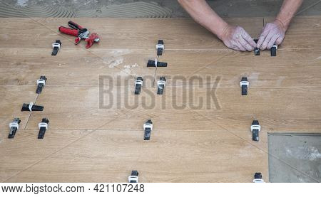 Tiler Lays Ceramic Tiles On The Floor. Tile Leveling Wedges, Tile Leveling System With Plastic Clips