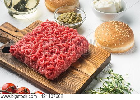 Fresh Raw Minced Beef Meat For Meatball Burgers With Sesame Buns Set, On Wooden Cutting Board, On Wh