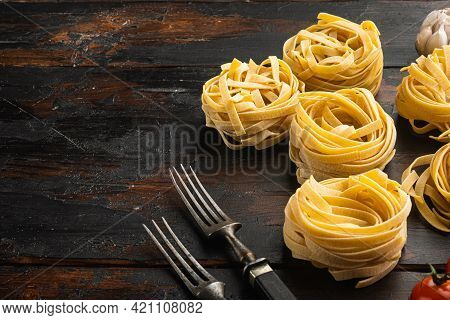 Rolled Tagliatelle Shape Of Italian Pasta With Ingredients Set, On Old Dark  Wooden Table Background