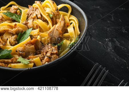 Tagliatelle With Chanterelles And Stewed Rabbit Set, In Bowl, On Black Stone Background