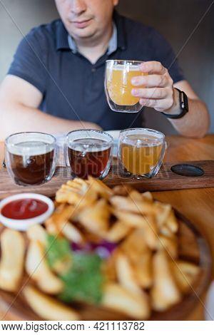 Man Sampling Variety Of Seasonal Craft Beer In Pub. Beer Samplers In Small Glasses Individually Plac