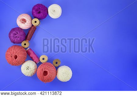 Crescent Moon Multicolored Balls And Bobbins Of Woolen Yarn, Sleeves Of Wooden Thread On Blue Backgr