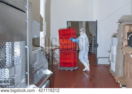 Factory For The Production Of Food From Meat.industrial Equipment At A Meat Factory.worker Moves Box