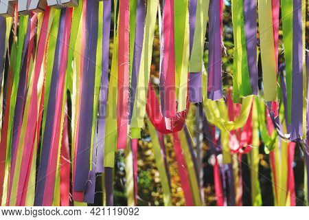 Many Beautiful Colorful Ribbons Hanging In Sunny Park At Street Food Festival, Close Up. Bright Happ