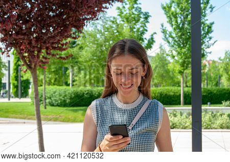 Portrait Of Brunette Woman Using Smartphone In The Park. Cell Phone In Hands. Caucasian Woman Smilin