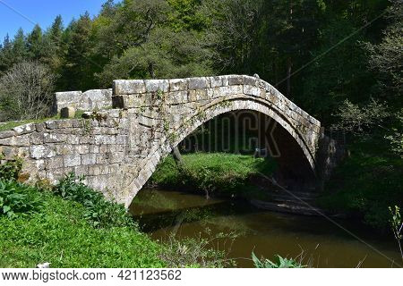 Stone Arched Beggar's Bridge Footpath Over The Water In Glaisdale England.