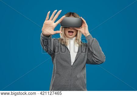 Excited Woman In Vr Headset Outstretching Hand And Touching Invisible Object While Experiencing Virt