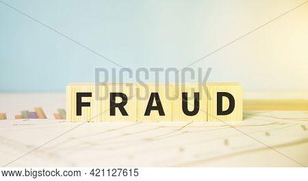 Fraud Word Written On Wood Block. Financial Fraud Concept.