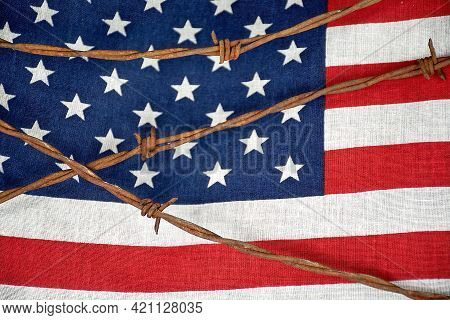 Close Up Of Rusty Barbed Wire Fencing On American Flag