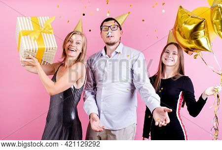 Birthday Party. Three Friends In Birthday Hats Celebrating Birthday Party Over Pink Background