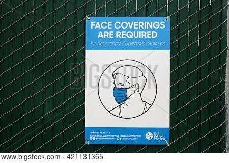 May 14, 2021 Santa Monica California, USA: Wear a Face Mask sign to stay safe from the Corona Virus. A sign posted on a fence to wear a mask to avoid Covid-19. Editorial Use.