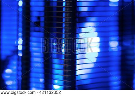 Cooling abstarct. Aluminum Radiator fins of  LED illuminated cooling fan, light coming through the radiator fins.  Cooling fan for computer and PC equipment. Extremely Shallow depth of field.