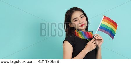 LGBTQ girl and pride flag. Sexy Lesbian girl and LGBT flag standing. blue green background. Asian LG