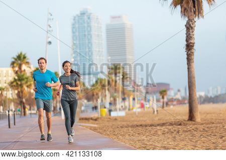 Running man and woman couple jogging on Barcelona Beach, Barceloneta. Healthy lifestyle people runners training outside on boardwalk. Multiracial couple, Asian woman, Caucasian fitness man working out