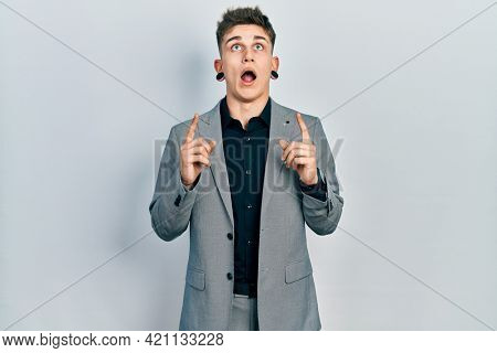 Young caucasian boy with ears dilation wearing business jacket amazed and surprised looking up and pointing with fingers and raised arms.