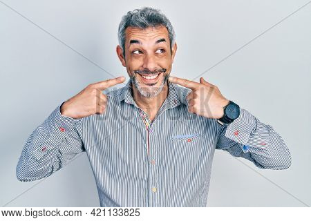 Handsome middle age man with grey hair pointing mouth with fingers smiling looking to the side and staring away thinking.