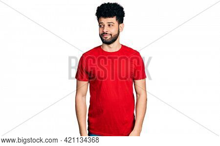 Young arab man with beard wearing casual red t shirt smiling looking to the side and staring away thinking.