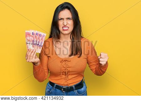 Beautiful hispanic woman holding south african 50 rand banknotes annoyed and frustrated shouting with anger, yelling crazy with anger and hand raised