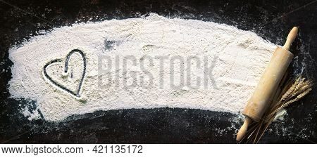 Baking background. Heart of flour and rolling pin on dark table with copy space, top view