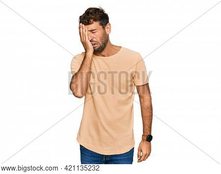 Handsome young man with beard wearing casual tshirt yawning tired covering half face, eye and mouth with hand. face hurts in pain.