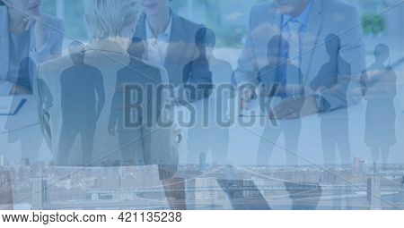 Composition of business people in meeting over people silhouettes. global business, success, deal and communication networking concept digitally generated image.