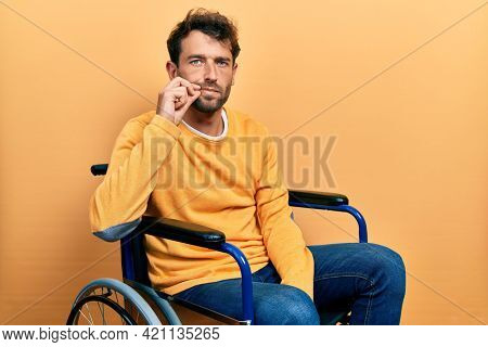 Handsome man with beard sitting on wheelchair mouth and lips shut as zip with fingers. secret and silent, taboo talking