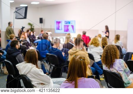 Unrecognizable female speaker standing on stage with presentation screen and explaining business ideas to entrepreneurs gathering in conference auditorium